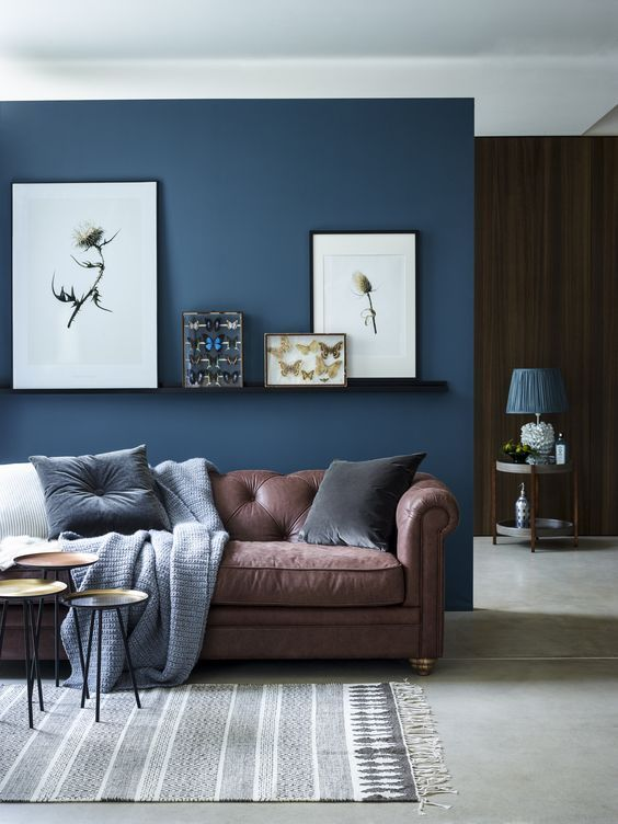 blue living room chic seating area with a brown sofa and a navy accent wall and CZXYWAJ