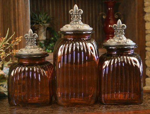 AMBER DECORATIVE GLASS CANISTER SET WITH FLEUR DE LIS LIDS (SET OF .