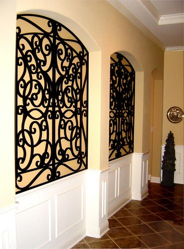 Inset wall niche - wrought iron in square niche with curved top .